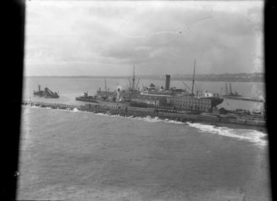 """""""NZ Shipping Co Rimutaka moored on East side of Moturoa Wharf, Rarawa on the west side, S.D. 'Paritutu' at the wharf end. Steam crane working at the end of the Main Breakwater."""""""