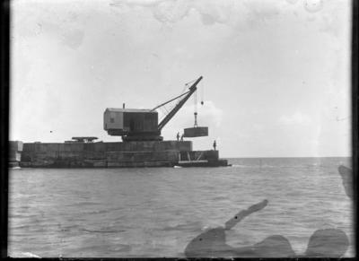 """""""Main Breakwater Extension 1924-1929. Crane lifting concrete block into place at the end of the Main Breakwater."""""""