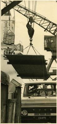 Crane suspending metal sheet above truck.